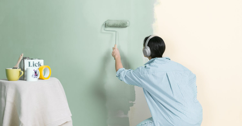 mujer pintando pared color olivo claro